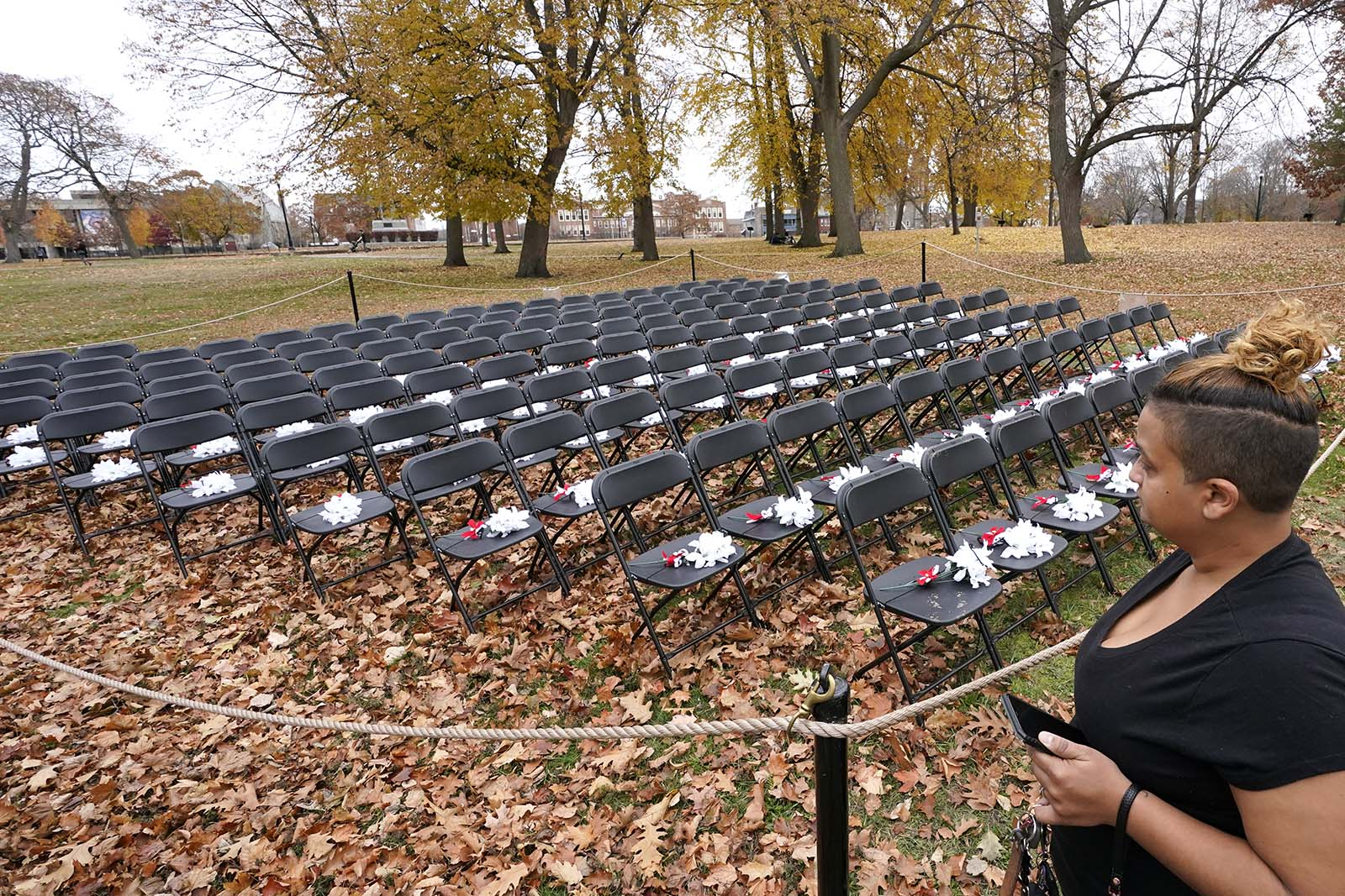 Eunice Lopez, of Lawrence, Massachusetts, looks at the COVID-19 Empty Chair Memorial on display at Campagnone Common, on Wednesday, November 11.