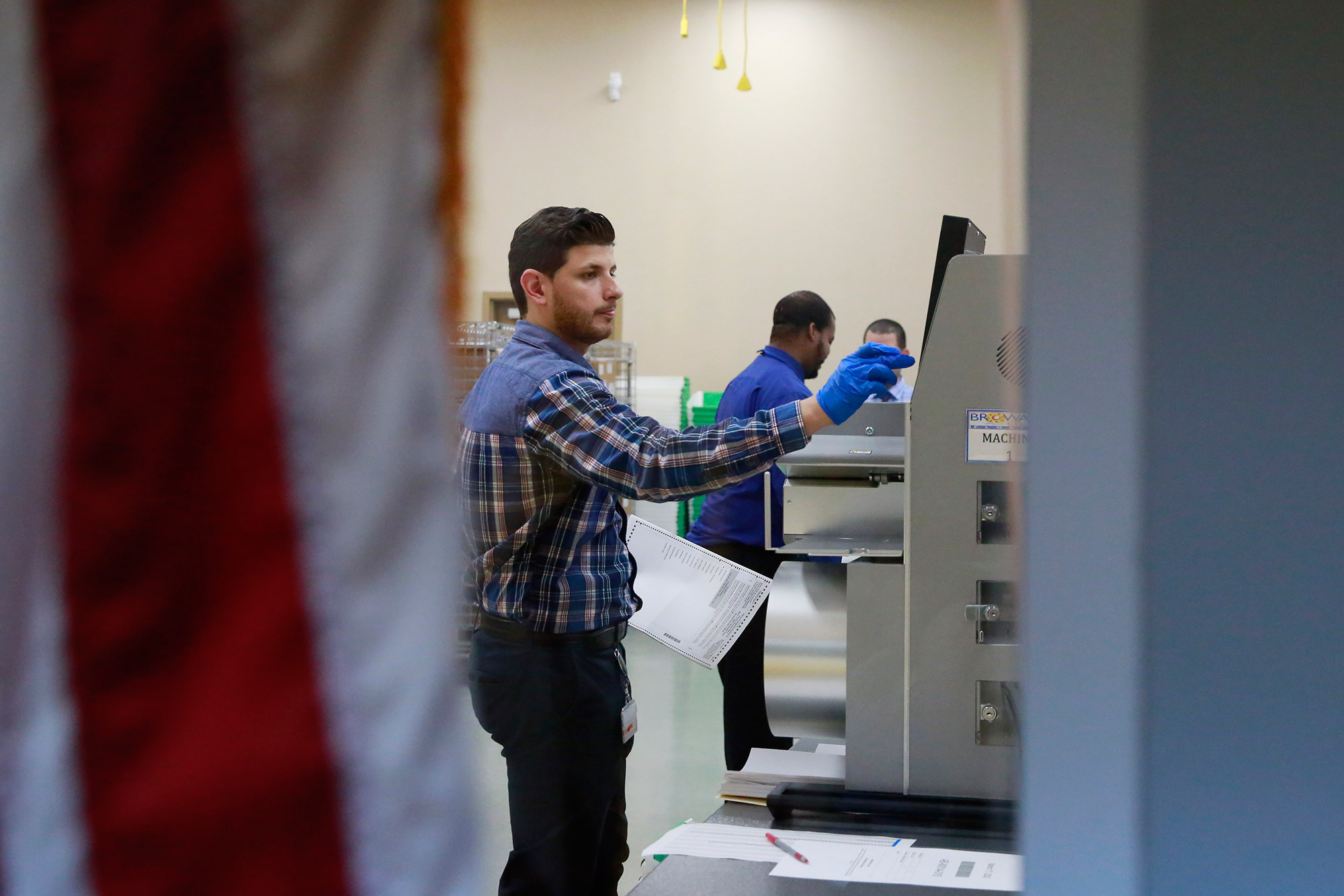 A worker wearing protective gloves counts ballots at the Broward County Supervisor of Elections Office during the Florida Primary elections, Tuesday, March 17, in Lauderhill, Florida.
