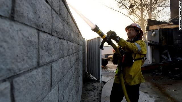 A firefighter hoses down a house on fire during the Tick fire in the Santa Clarita area of Los Angeles, Calif. on Thursday, Oct. 24.
