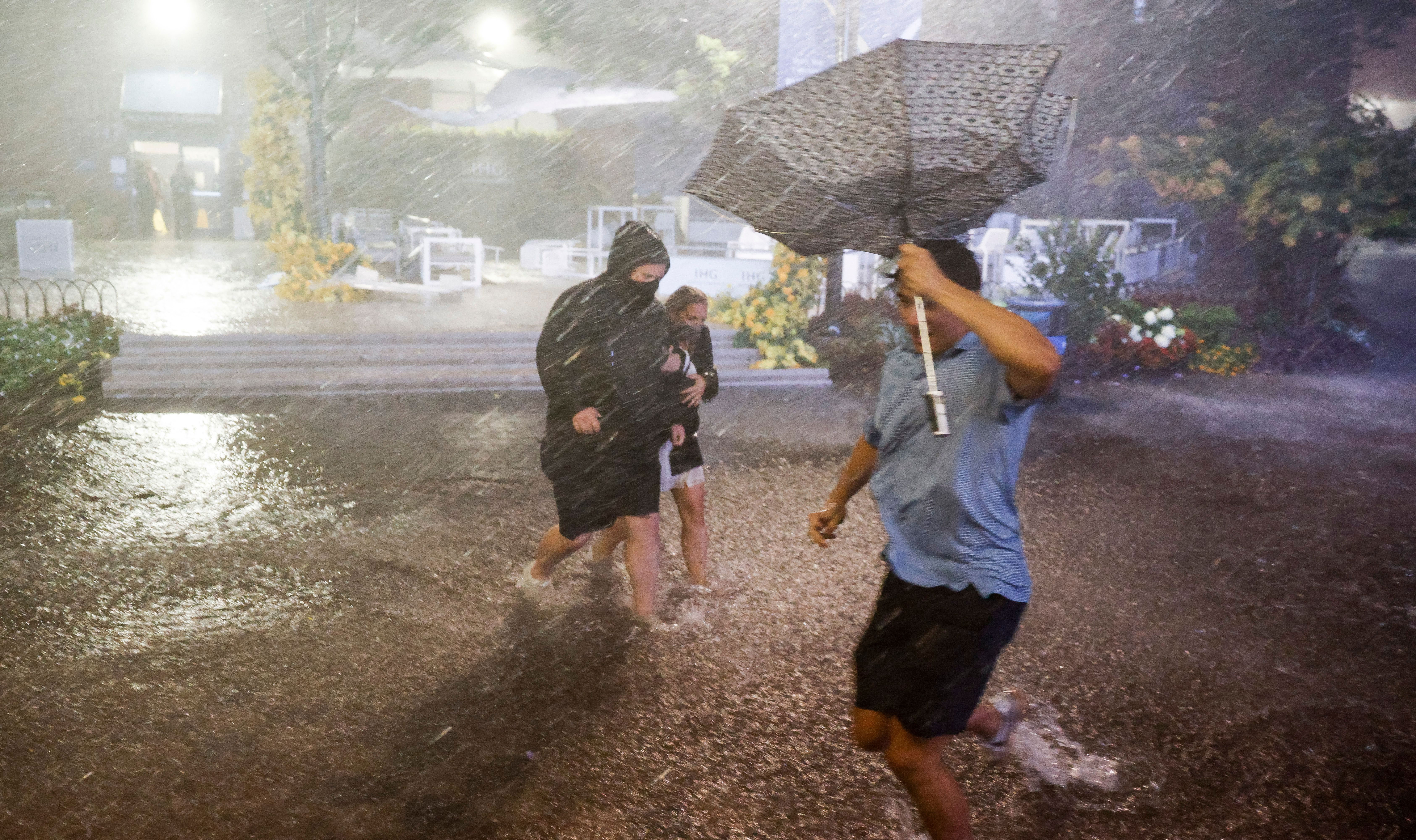 People navigate heavy rains and flooded walkways at the Billie Jean King National Tennis Center in Queens, New York, on September 1.