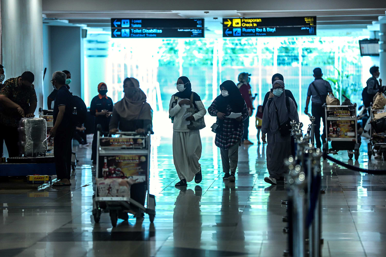 Travelers arrive at Sultan Mahmud Badaruddin II airport in Palembang, Indonesia on December 23.