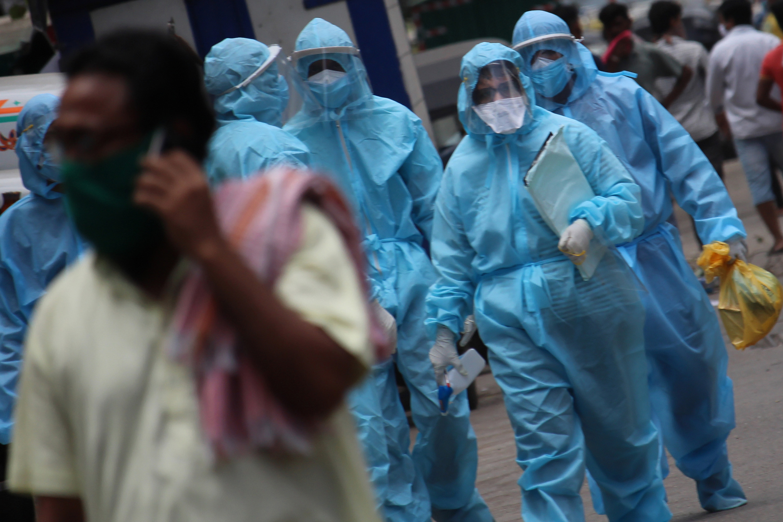 Healthcare workers wearing protective suits walk along a street in the Dharavi slum area of Mumbai, India on Sunday, June 7.