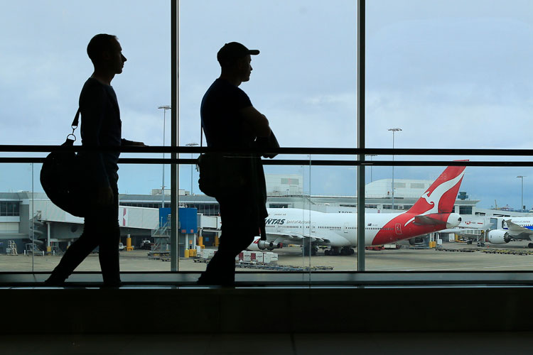 Two passengers walk past a Qantas jet at the International terminal at Sydney Airport on March 10 in Sydney, Australia.