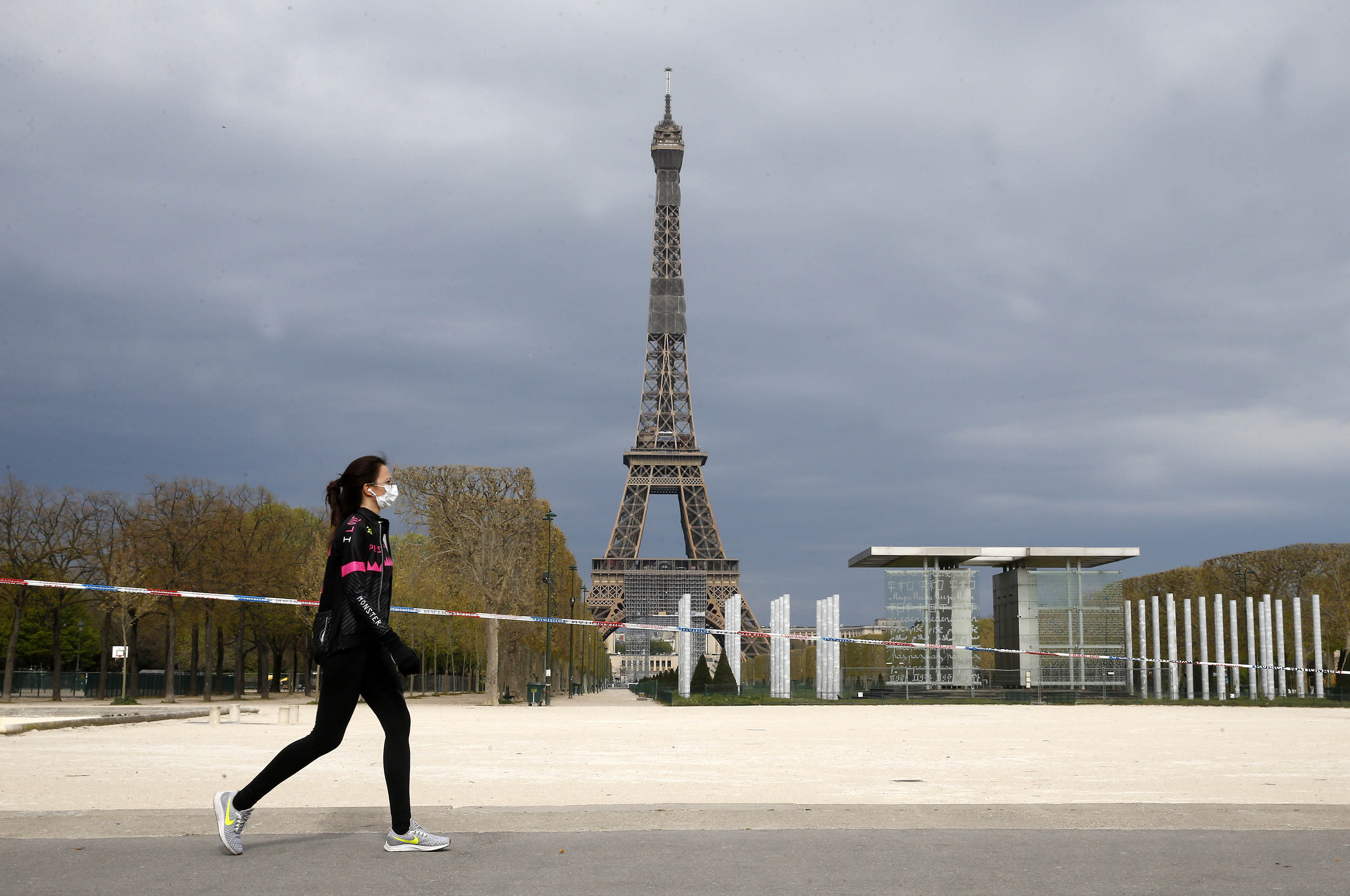 A woman walks passed the Eiffel Tower in Paris, France, on April 6.