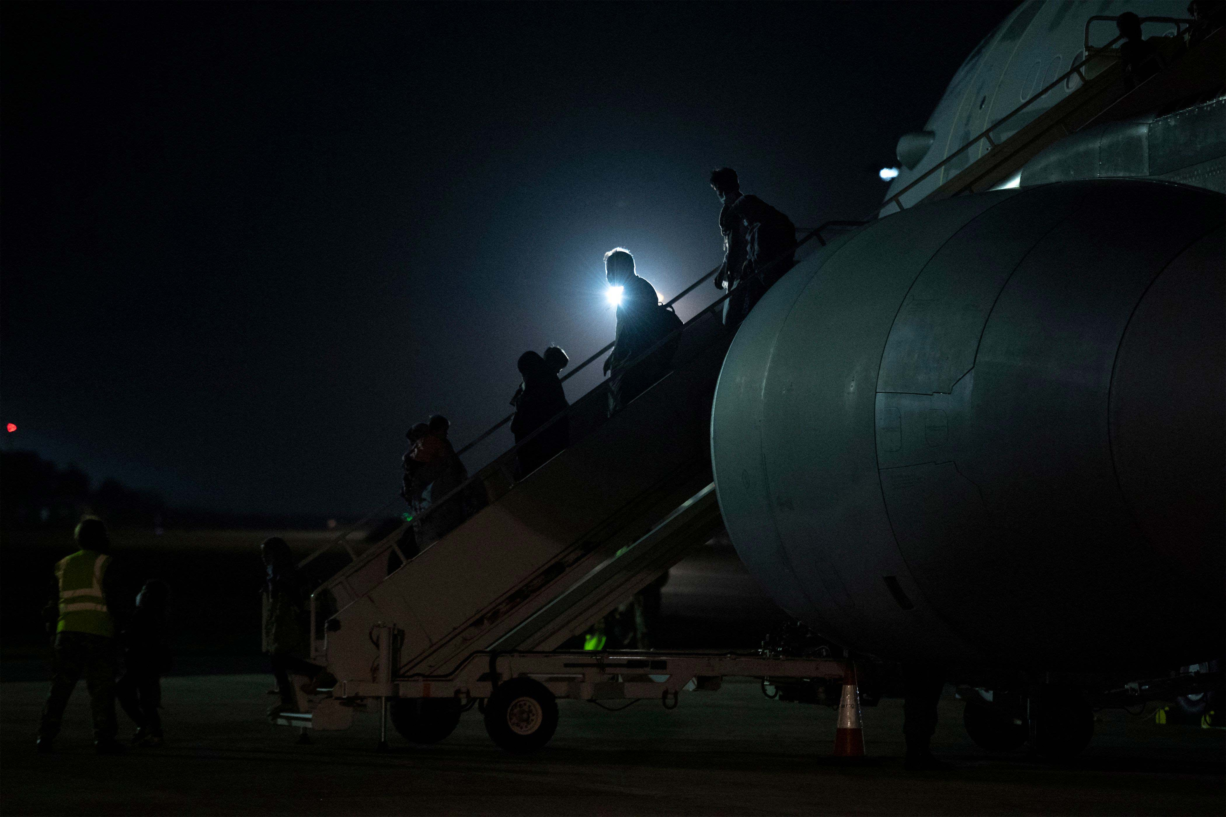 Passengers evacuated from Afghanistan disembark from a British Royal Air Force aircraft after landing at RAF Brize Norton station in England on August 24.