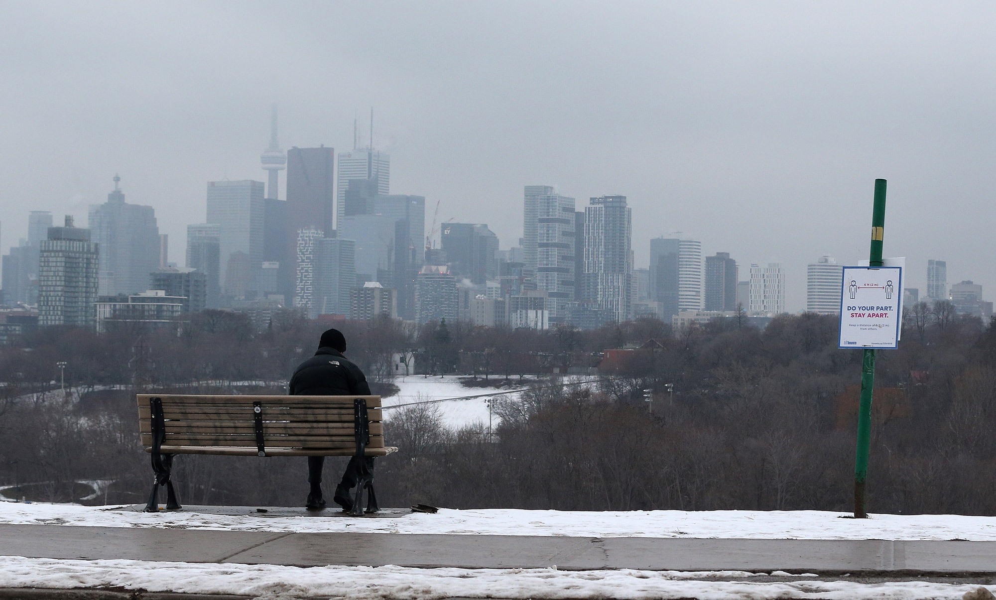 A man sits on a bench at Riverdale Park East in Toronto, Ontario, on January 5.