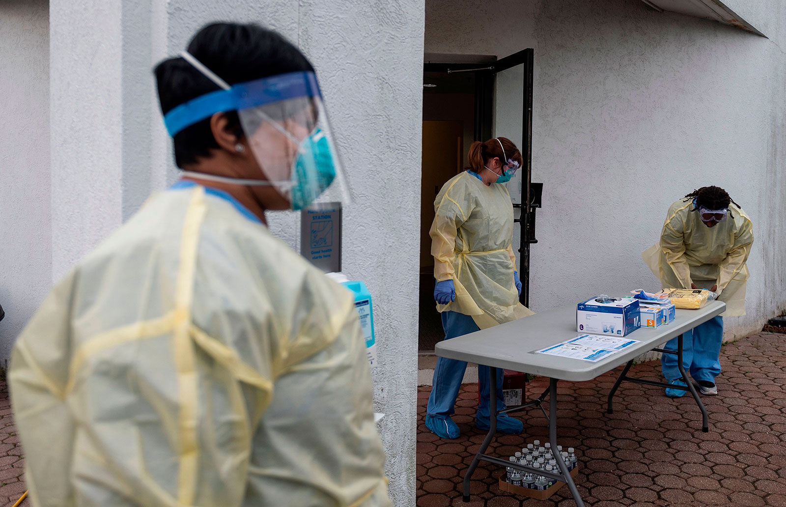 Health care workers put on personal protective equipment at a drive-through testing site in Arlington, Virginia, on March 20, 2020.