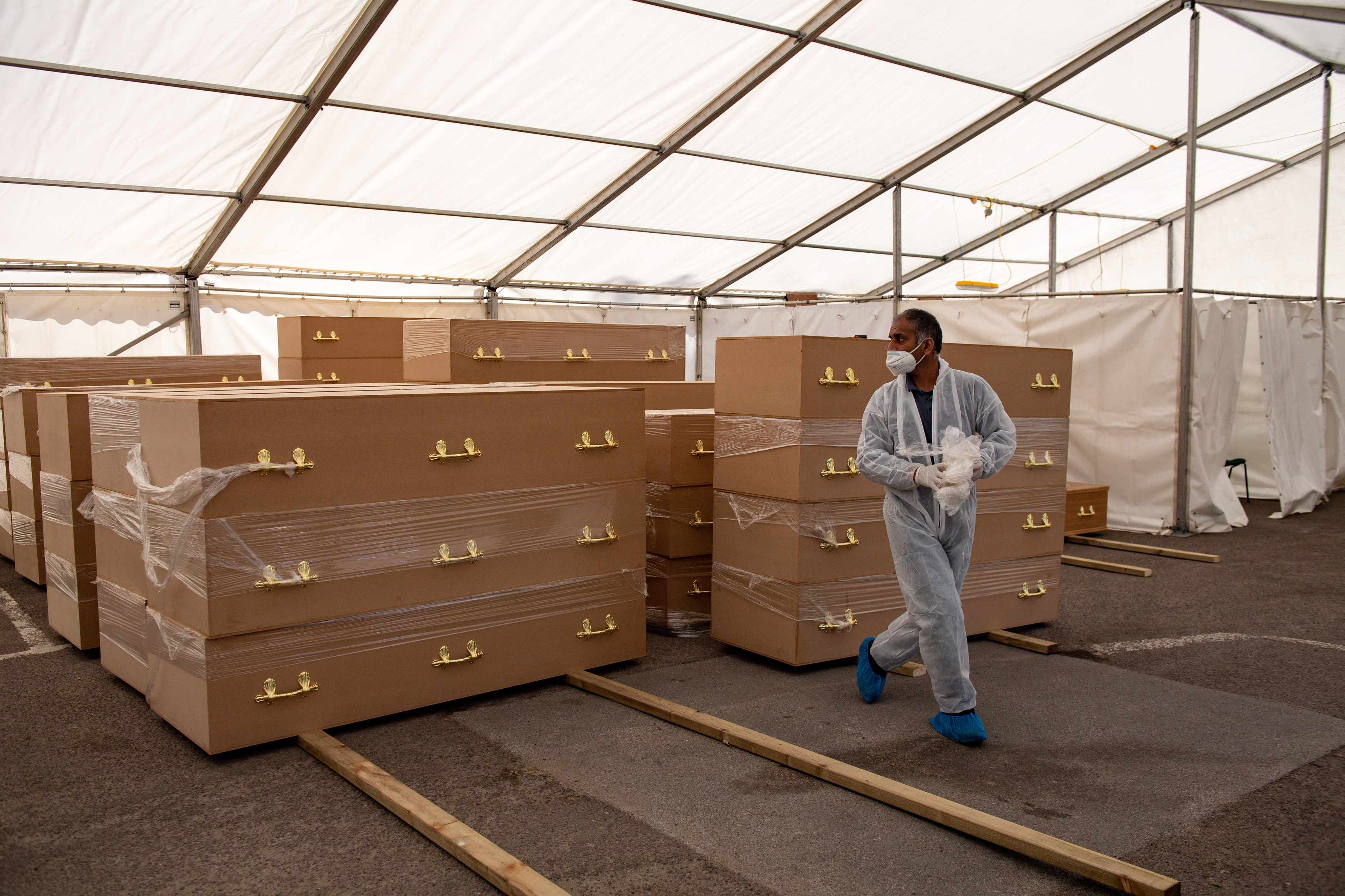 A volunteer walks by coffins at Central Jamia Mosque Ghamkol Sharif in Birmingham, which is operating a temporary morgue during the Covid-19 pandemic.