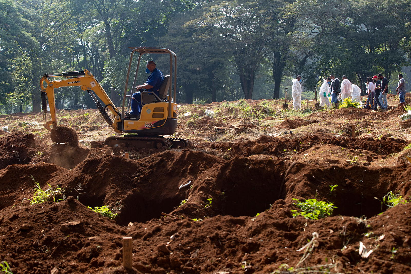 An employee uses a bulldozer to prepare more graves in Sao Paulo, Brazil, on March 11.
