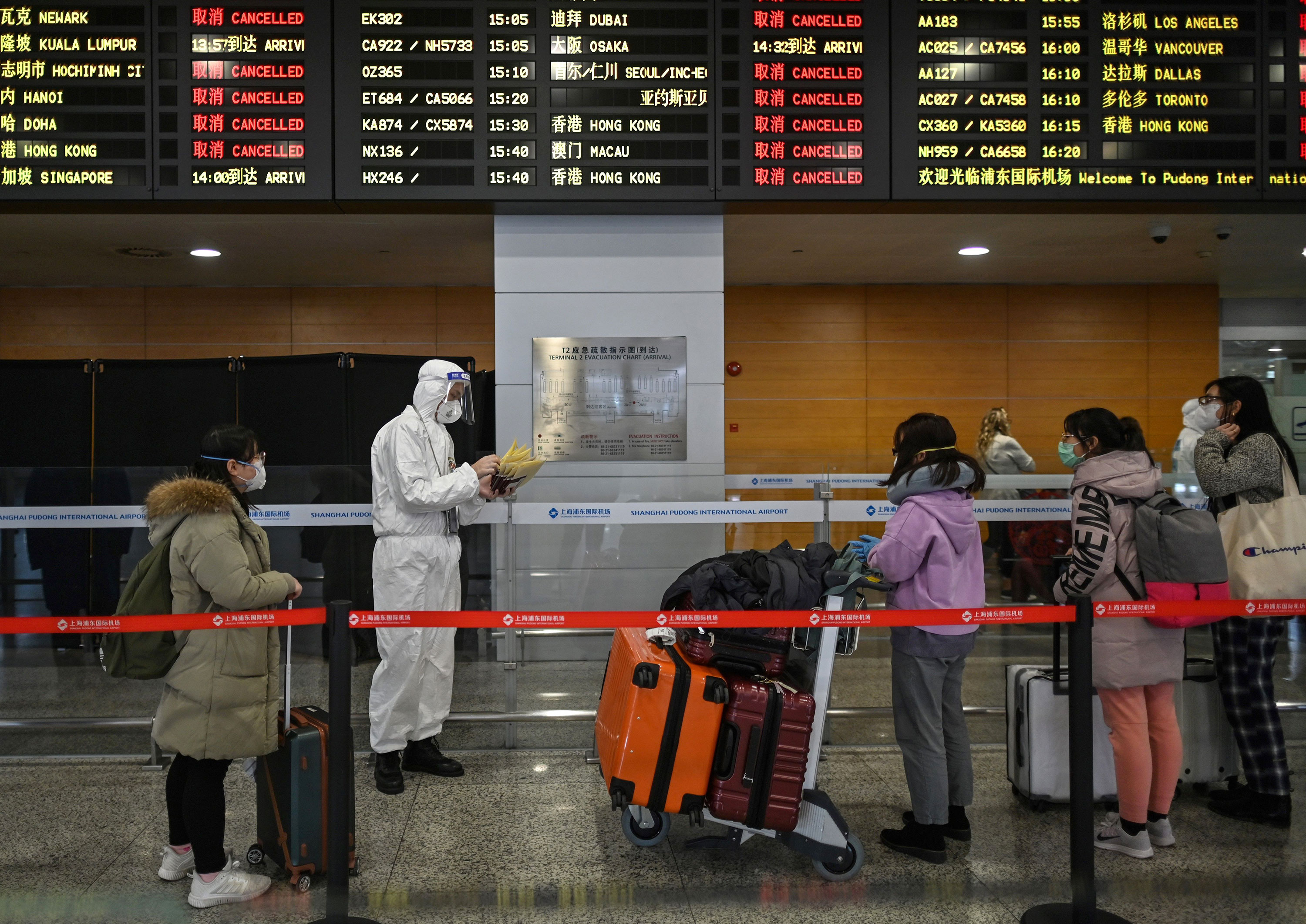 An airport security staff member assists passengers arriving to the Shanghai Pudong International Airport in Shanghai on March 19.