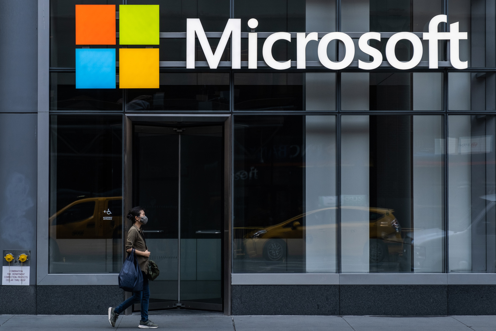 A pedestrian walks past a Microsoft Technology Center in New York City on July 22.