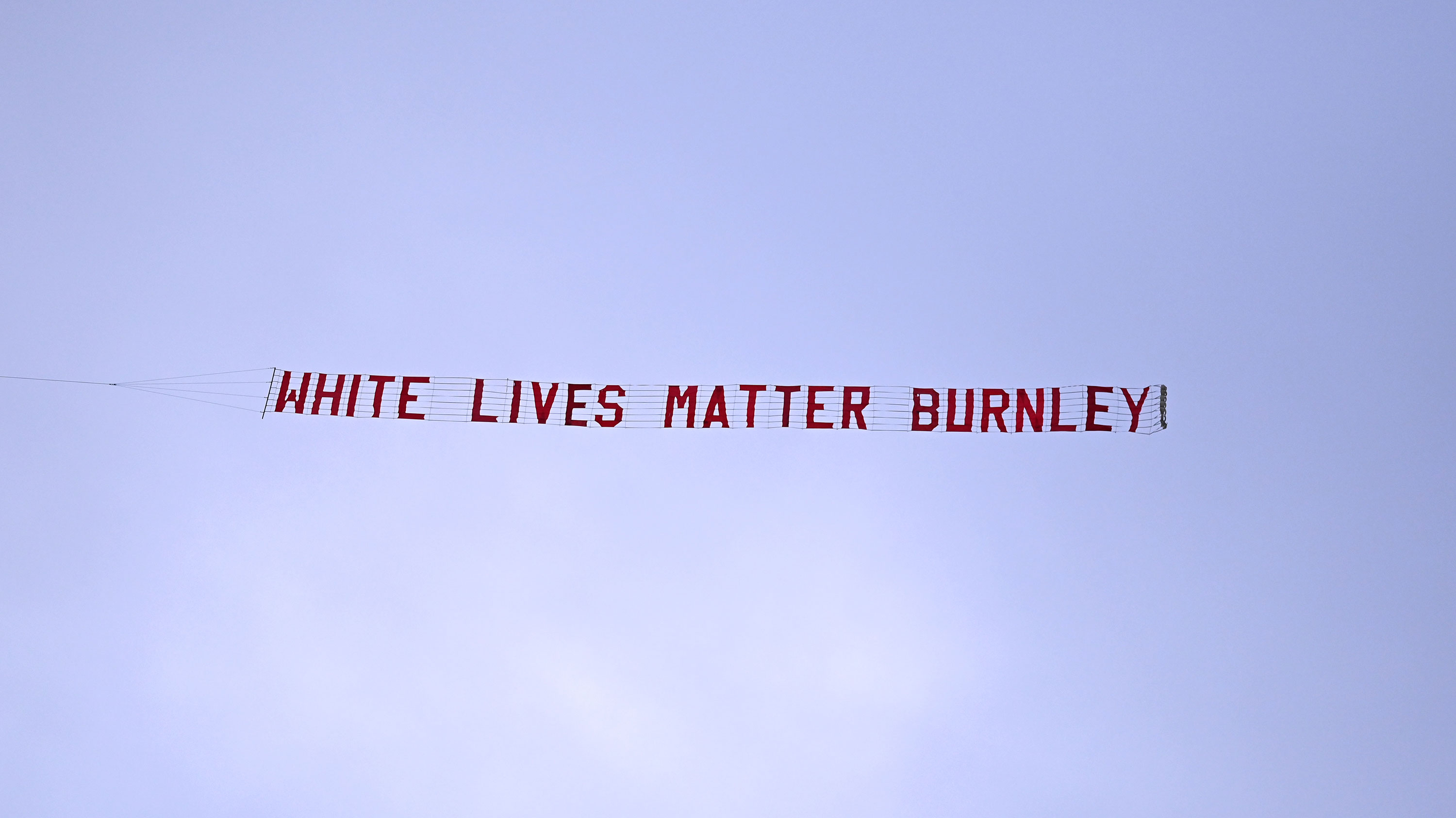 A plane flies over Etihad Stadium with a banner reading 'White Lives Matter Burnley' prior to the match between Manchester City and Burnley FC on June 22 in Manchester, England.