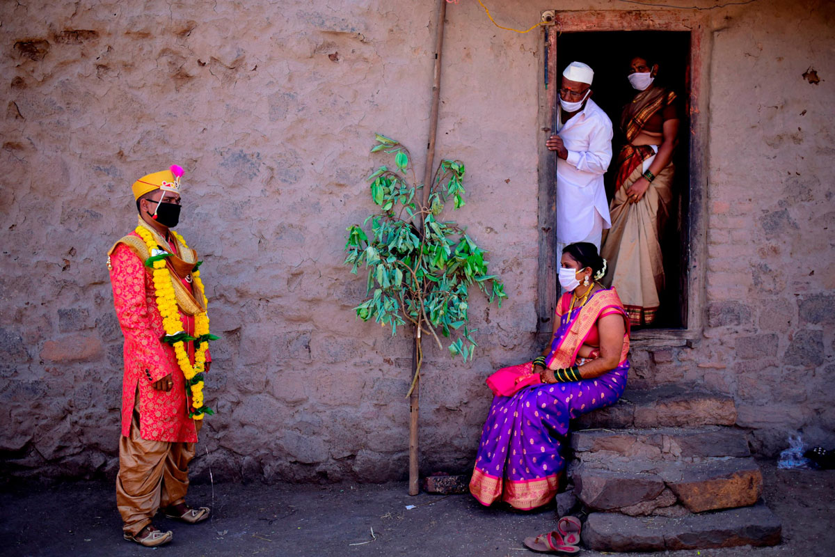 A groom speaks with his bride and family members following their wedding during a government-imposed nationwide lockdown in Pune, India.