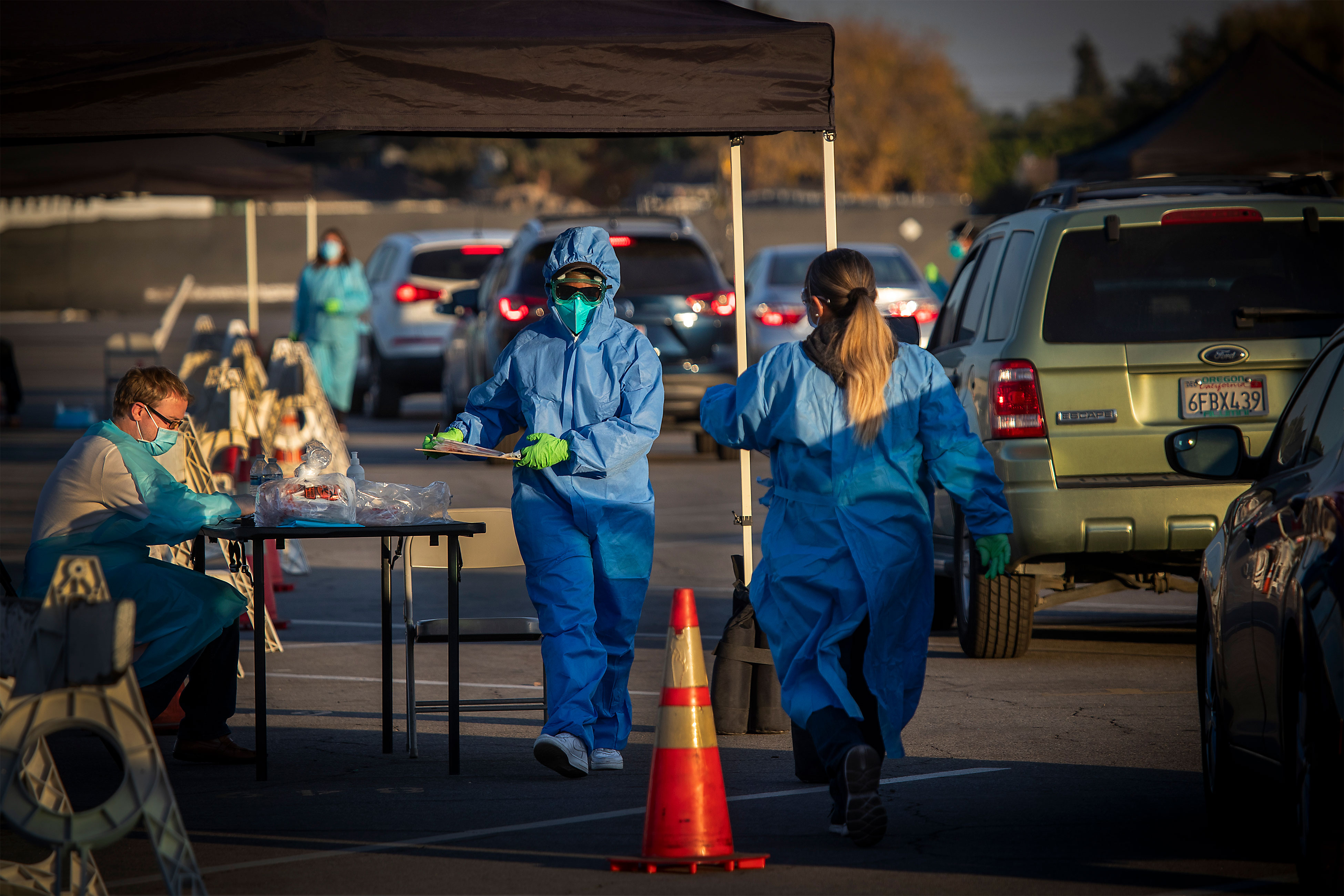 Health care workers in Long Beach, California, prepare and hand out Covid-19 self-administered tests on December 9.