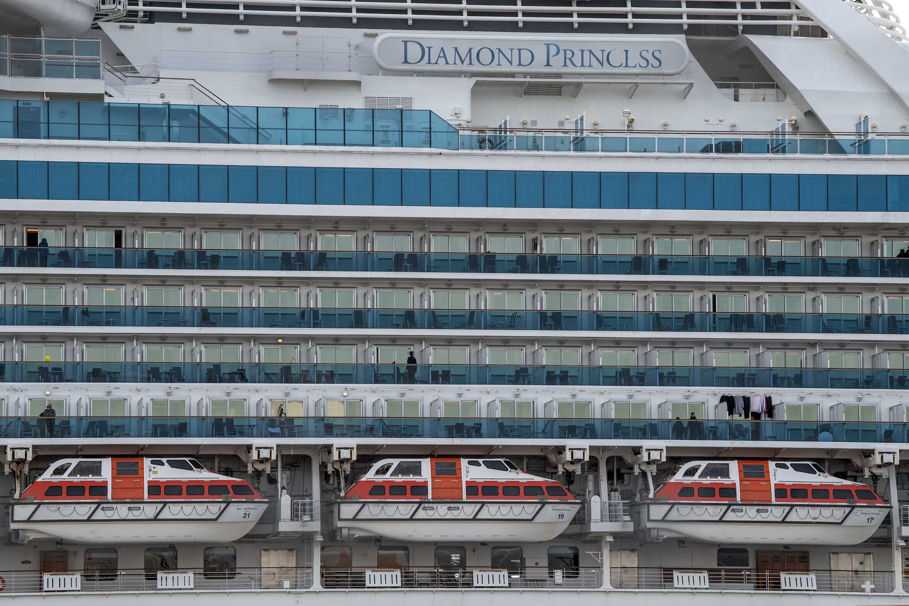 People stand on balconies aboard the Diamond Princess cruise ship docked at Daikoku Pier in Yokohama, Japan on Friday.