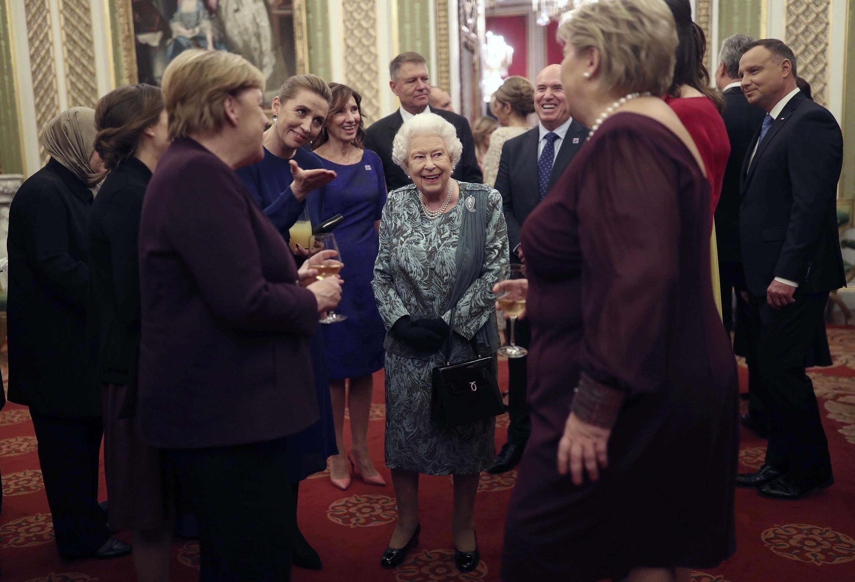 The British monarch talks to guests including German Chancellor Angela Merkel during the reception. Photo: Yui Mok/Pool via AP