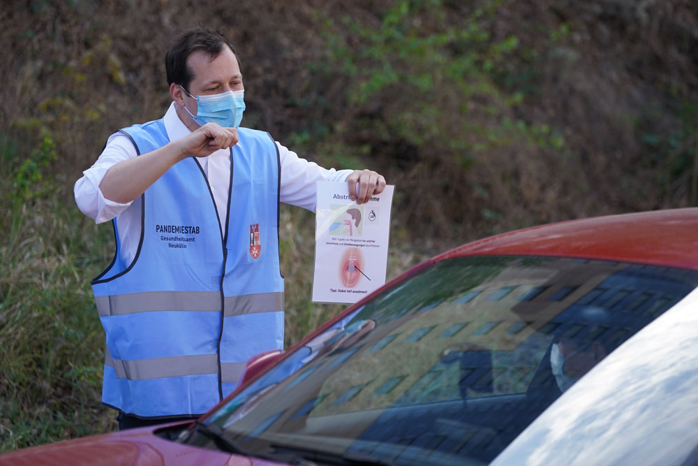 A medical worker instructs a woman in a car how to take a throat swab at a coronavirus testing facility in Berlin on April 24.