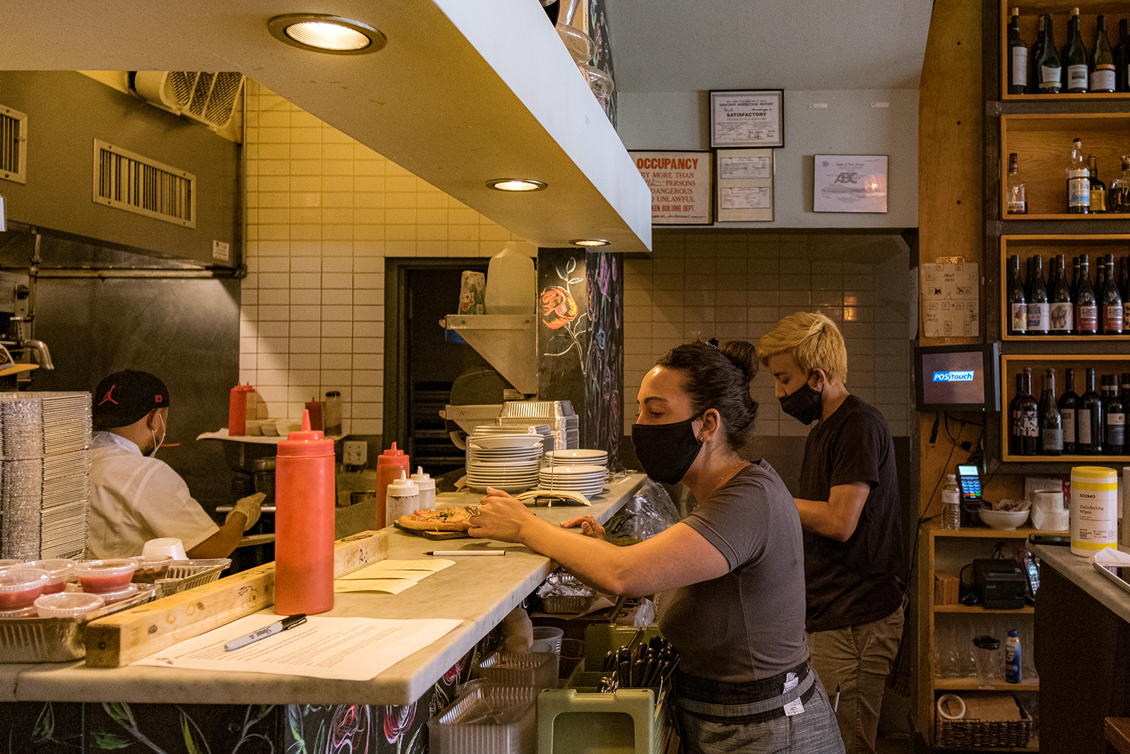 Restaurant staff wearing the protective masks work in the kitchen as the city reopens from the coronavirus lockdown on June 15 in Hoboken, New Jersey.