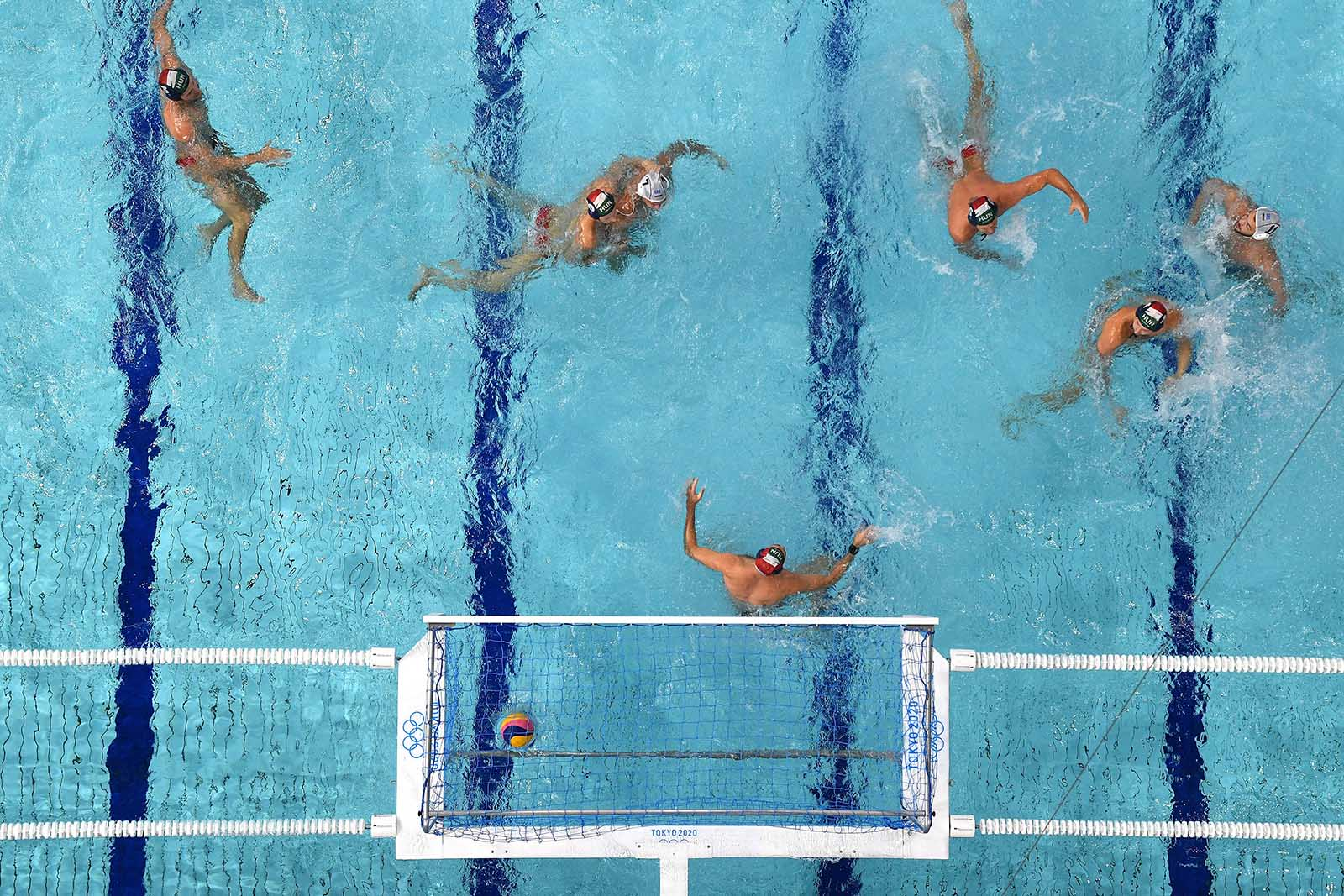 An overview shows Hungary's Viktor Nagy conceding a goal to Greece during the men's water polo semi-final match on August 6.