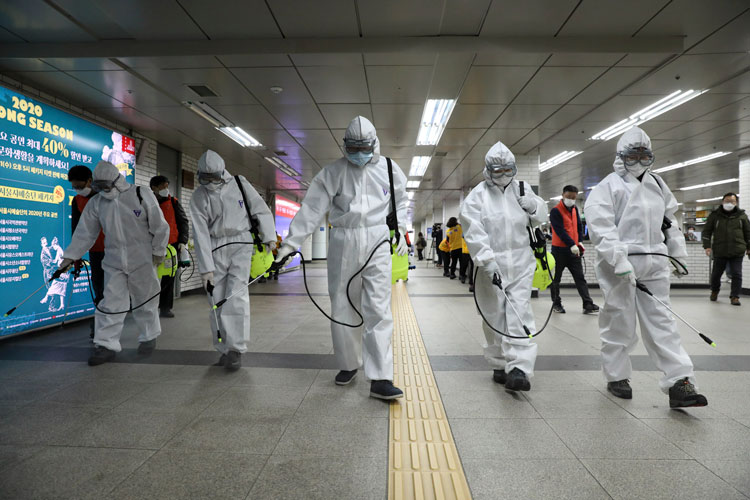 Workers wearing protective gear disinfect as a precaution against coronavirus at a subway station in Seoul on Wednesday, March 11.