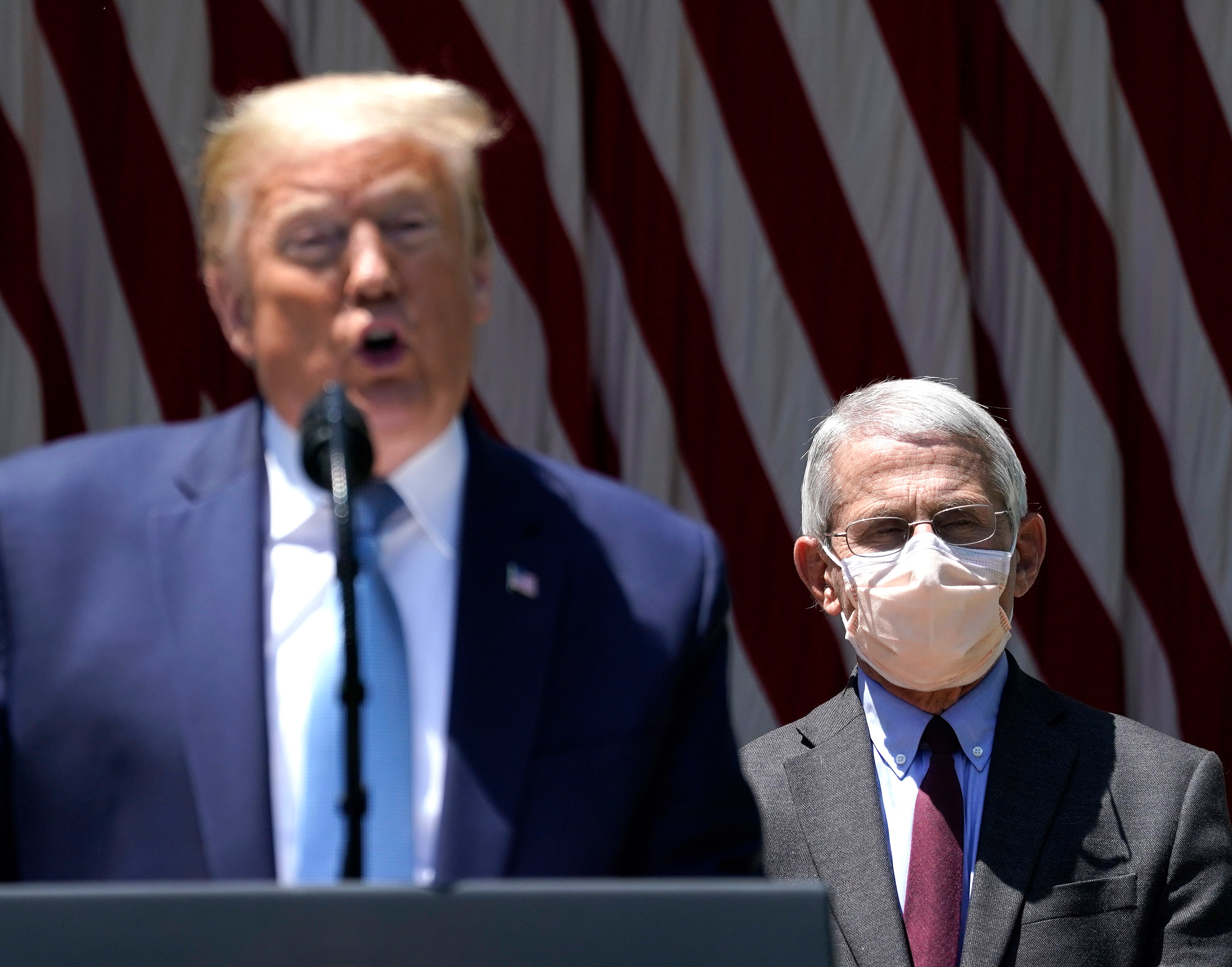 President Donald Trump is flanked by Dr. Anthony Fauci, director of the National Institute of Allergy and Infectious Diseases, while speaking in the Rose Garden of the White House on May 15 in Washington.