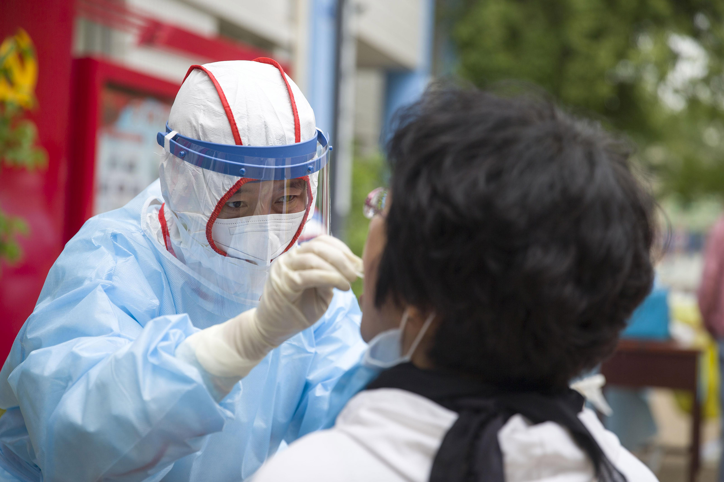 A medical worker wearing personal protective equipment (PPE) collects samples from a teacher for nucleic acid testing for the coronavirus at a primary school in Taiyuan, China, on Wednesday, May 13.