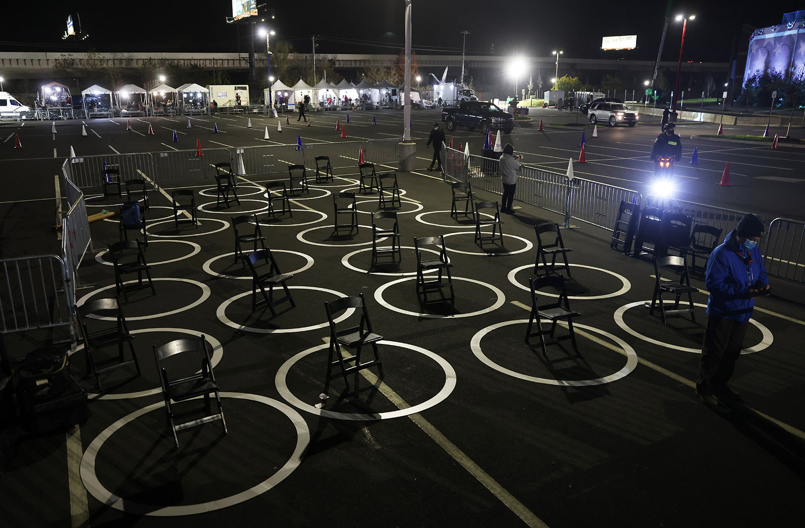 Chairs sit ready for reporters inside circles marked for social distancing as a Covid-19 precaution in the press area at a drive-in election night event for Democratic presidential nominee Joe Biden at the Chase Center.