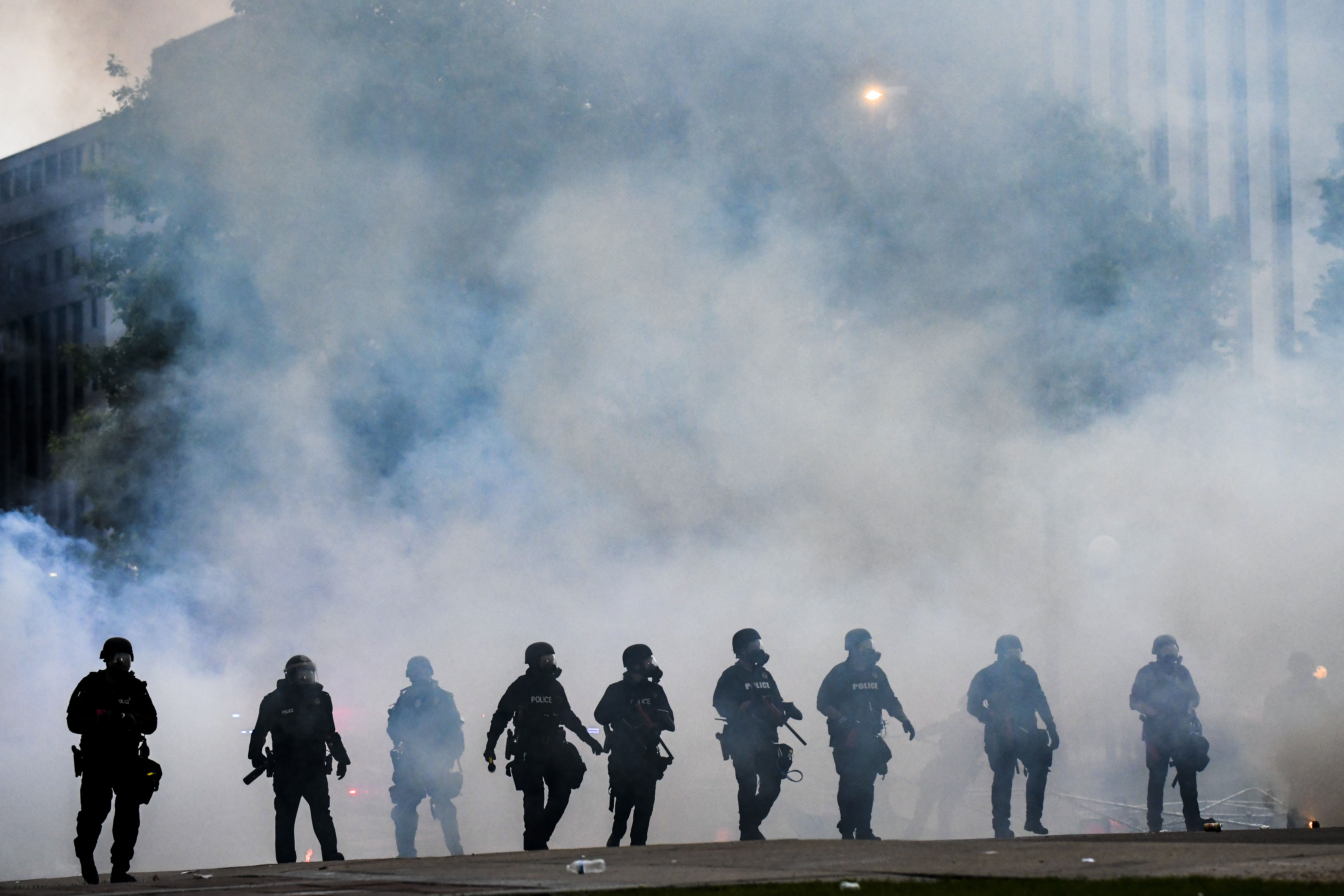 Police officers walk through a cloud of tear gas as they try to disperse protesters in front of the Colorado Capitol  in Denver on May 30.