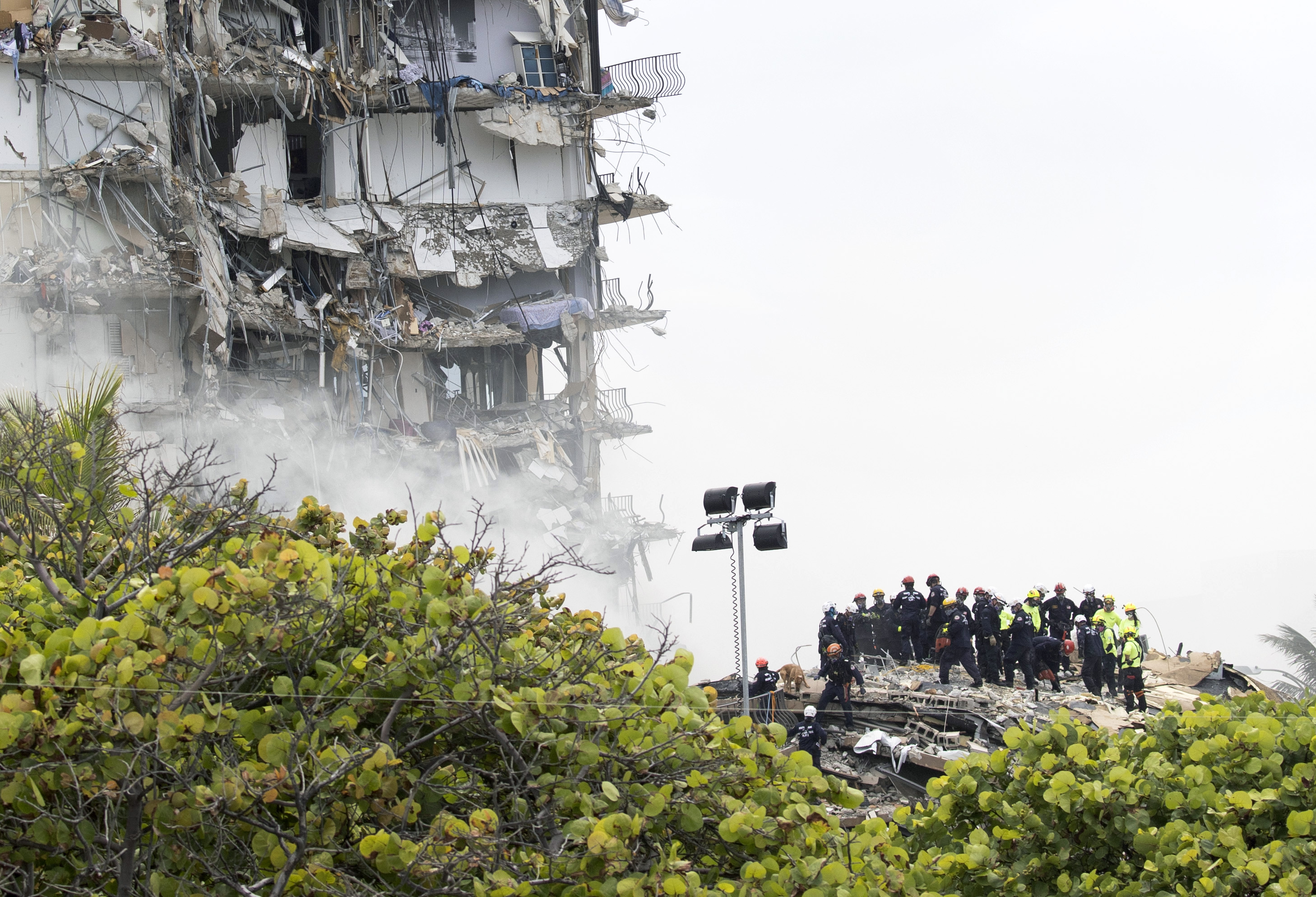 Members of the South Florida Urban Search and Rescue team look for possible survivors in the partially collapsed 12-story Champlain Towers South condo building on June 25 in Surfside, Florida.