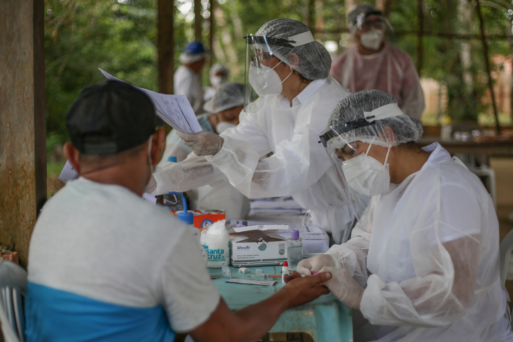 A nurse performs a coronavirus test to a resident of the riverside community of Belavista do Jaraqui on May 29 in Brazil.