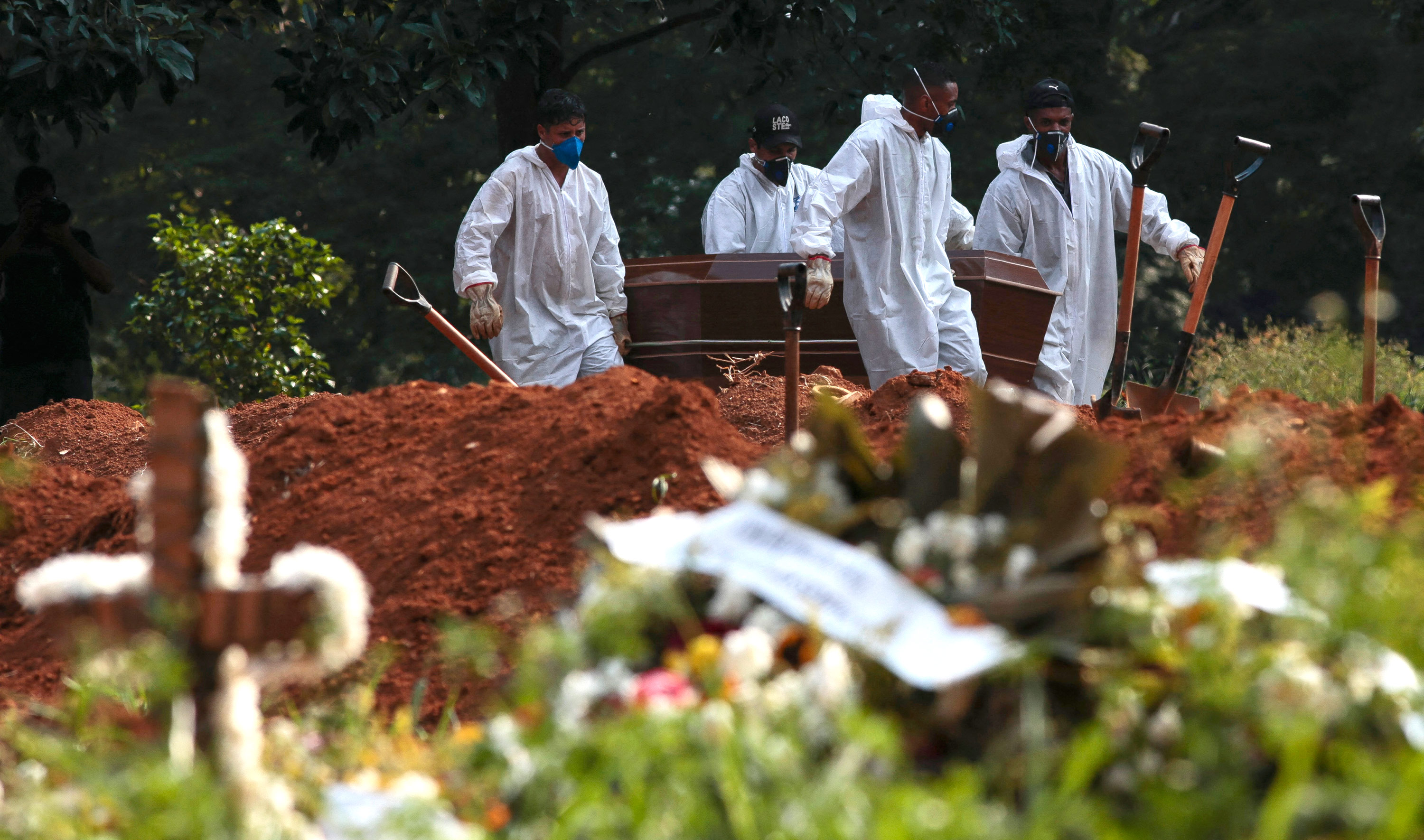 Cemetery workers carry the coffin of a Covid-19 victim at the Vila Formosa cemetery in Sao Paulo, Brazil, on March 23.