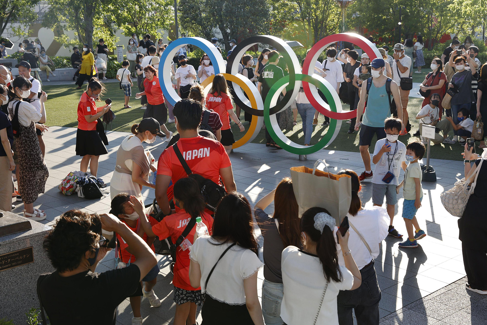 People take photos with the Olympic rings near the National Stadium in Tokyo on Saturday.