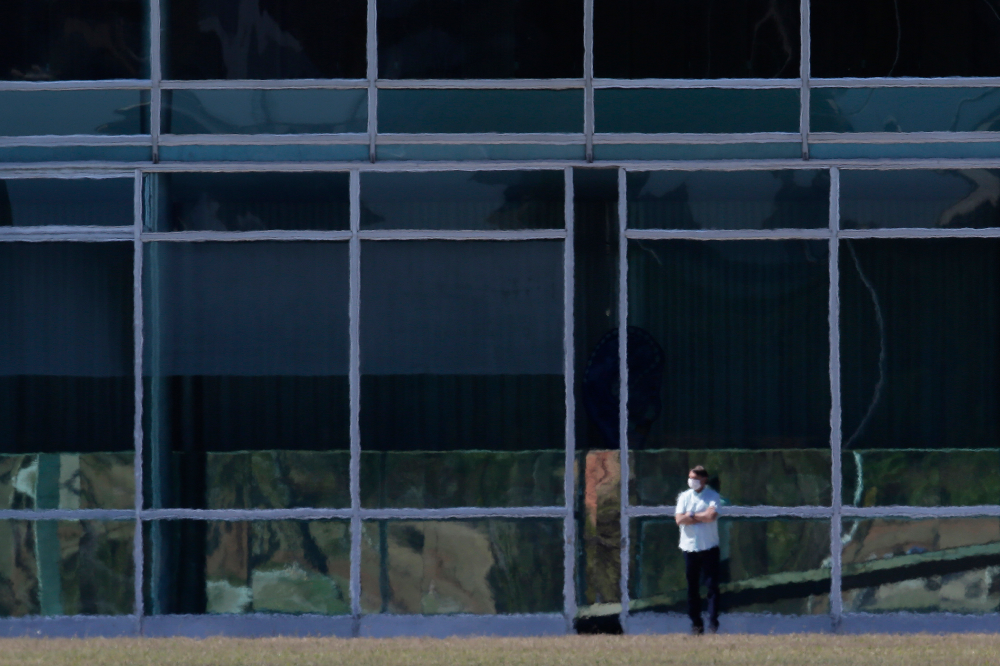 Brazil's President Jair Bolsonaro stands with his arms crossed outside the official presidential residence, Alvorada Palace, in Brasilia, Brazil, Wednesday, July 8.