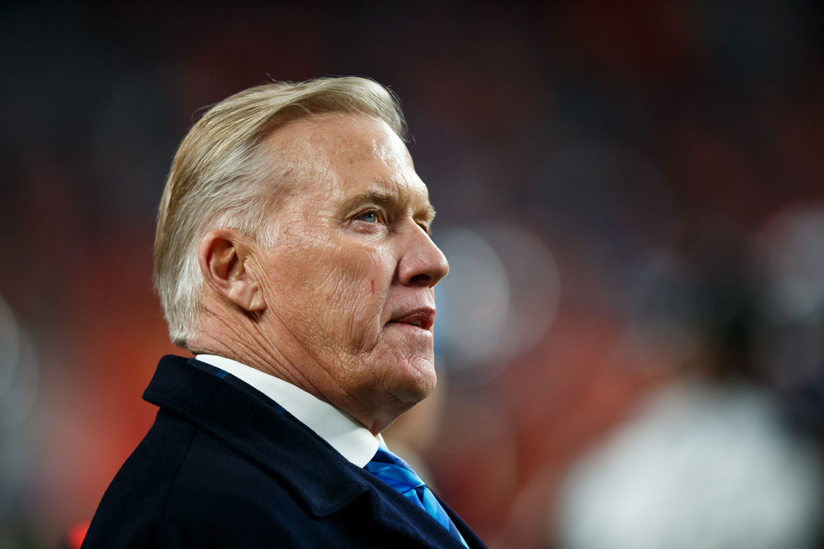 John Elway, President of Football Operations/General Manager for the Denver Broncos, stands on the sideline of a 2019 Broncos game.