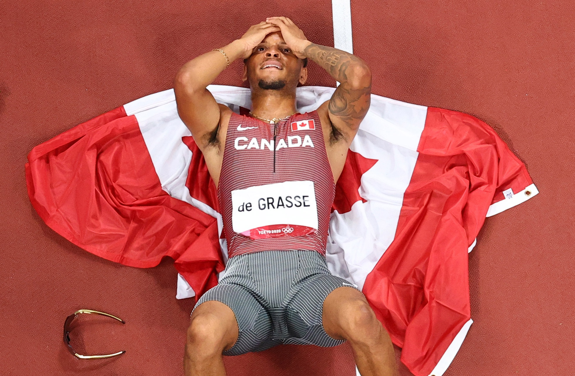 Canadian sprinter Andre De Grasse lies on the track after winning the 200-meter final on Wednesday, August 4. It's the first Olympic gold for De Grasse, who now has five medals in all.