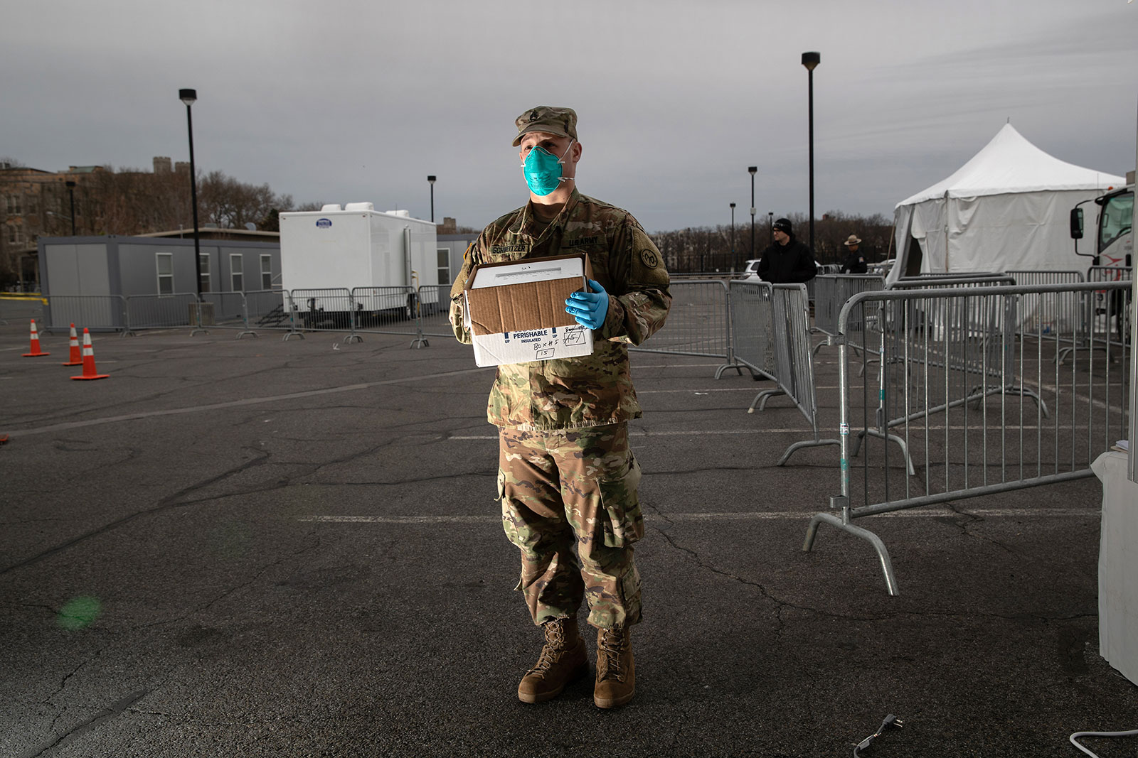 A National Guard soldier holds a case of fresh coronavirus tests at a drive-through testing center at Lehman College in New York City on March 28.