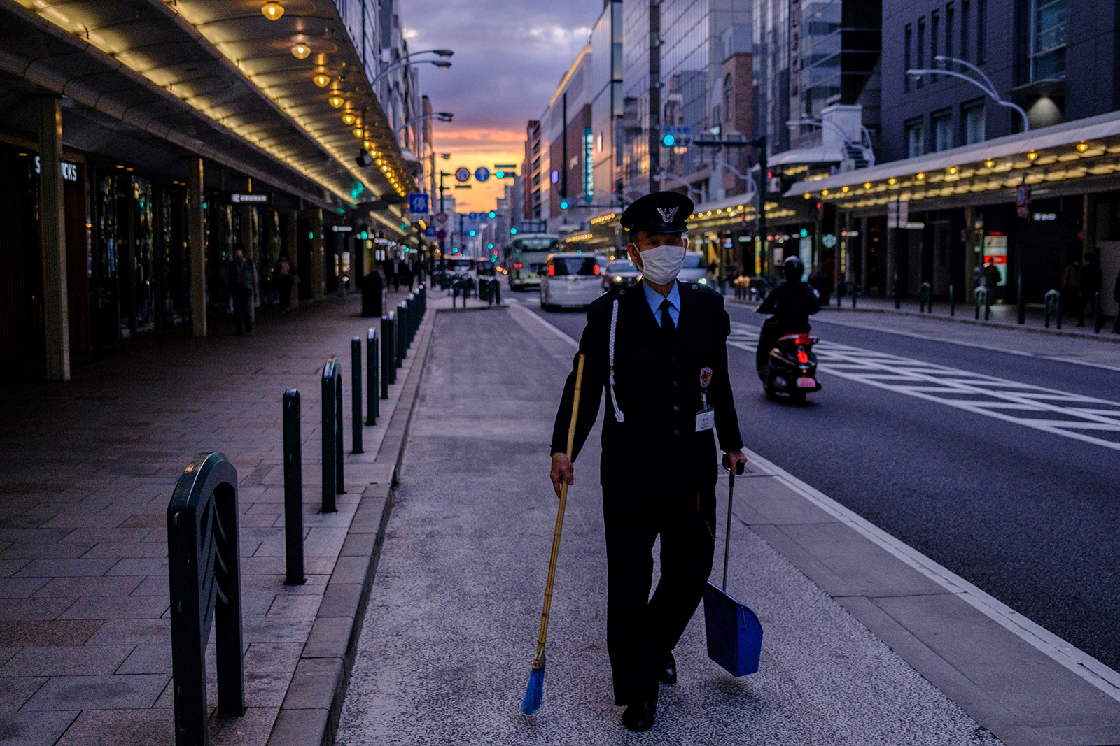 A security guard wearing a face mask walks with a broom in Kyoto on May 21.
