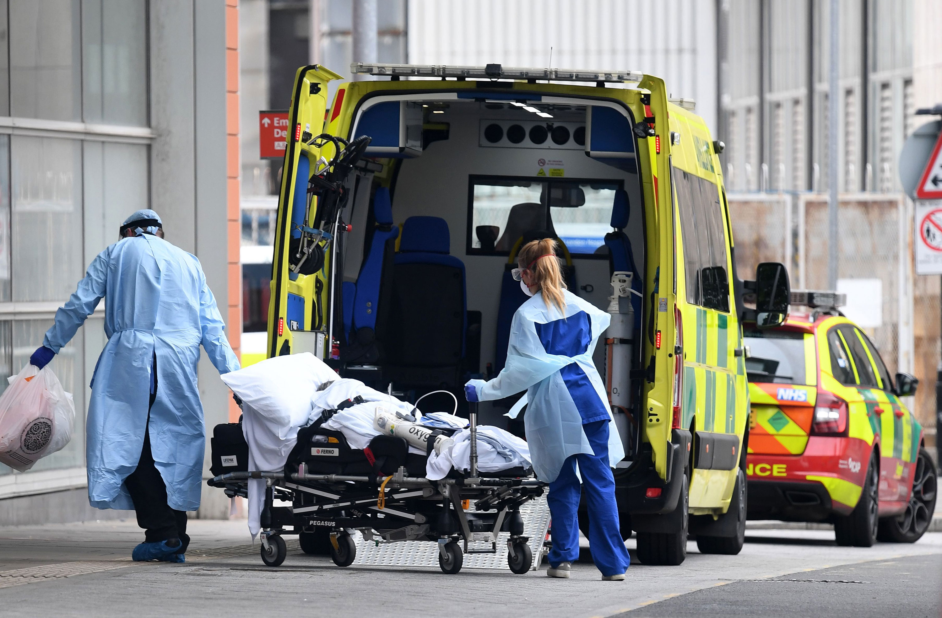 Health workers transfer a patient from an ambulance into The Royal London Hospital in London on April 18.