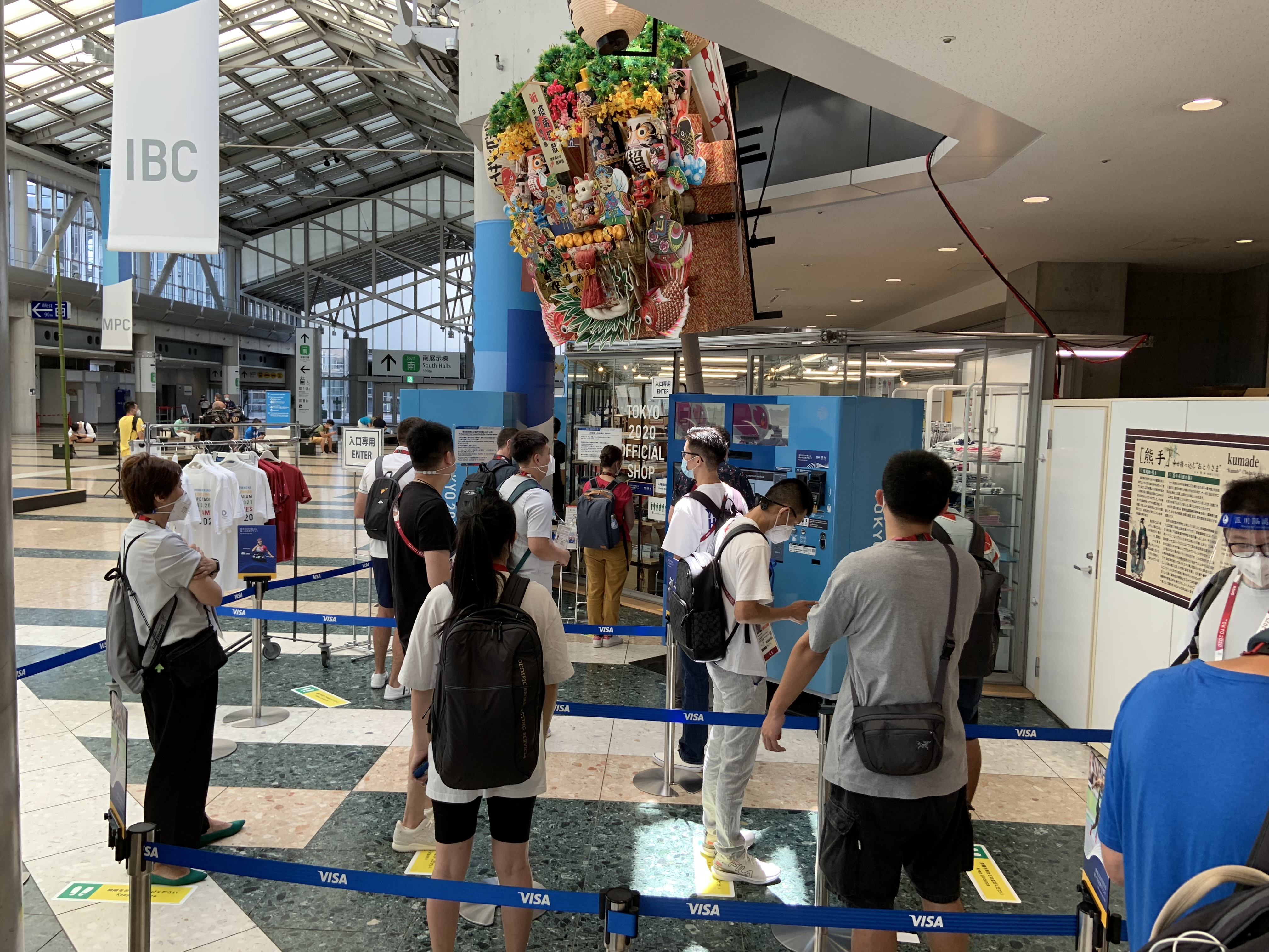 People line up to use an Olympic souvenir vending machine at the main press center in Tokyo.