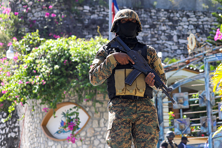 A Haitian police officer stands guard outside of the presidential residence on July 7,  in Port-au-Prince, Haiti.