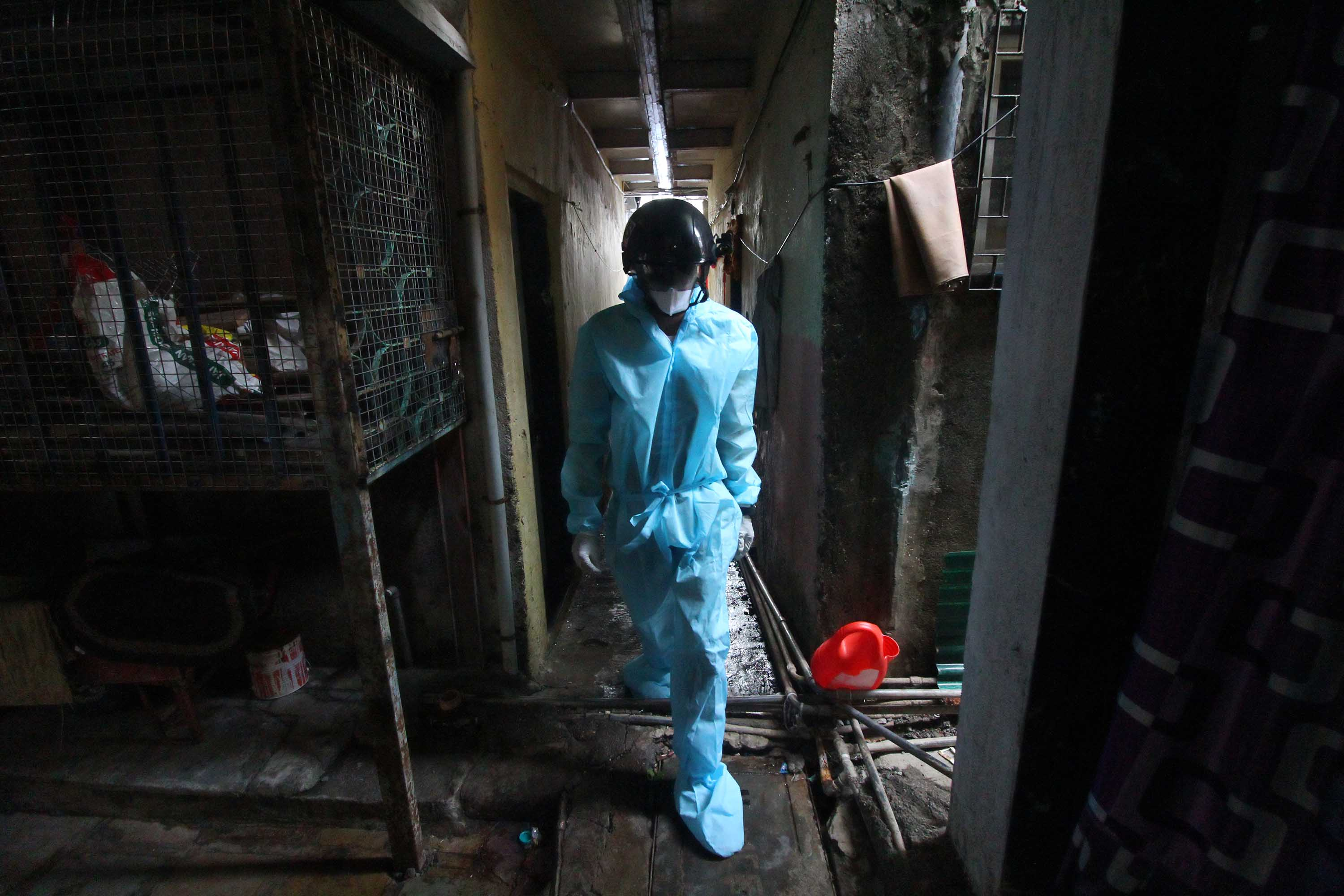 A health care worker walks through an alley of a Mumbai slum during a medical check-up on July 20.