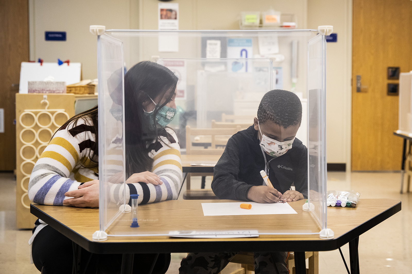 Pre-kindergarten teacher Sarah McCarthy works with a student at Dawes Elementary in Chicago on Monday, January 11.