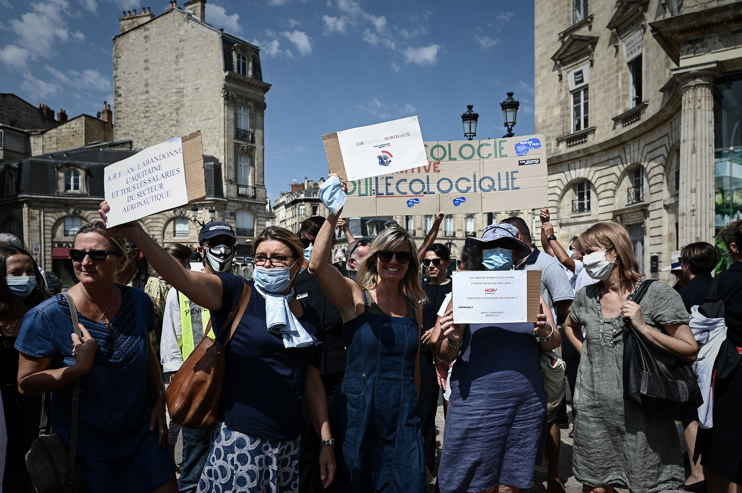 Women hold signs as HOP! and Air France employees protest against the end of the air shuttle service between Bordeaux-Mérignac and Paris-Orly outside Air France offices in Bordeaux, south-western France, on Friday, July 30.