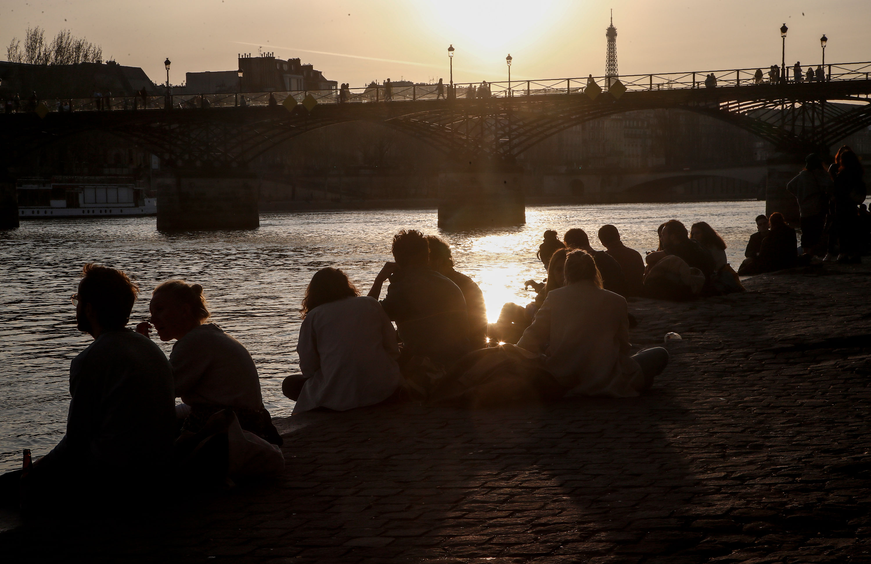 People sit along the Seine river bank in Paris on March 24.