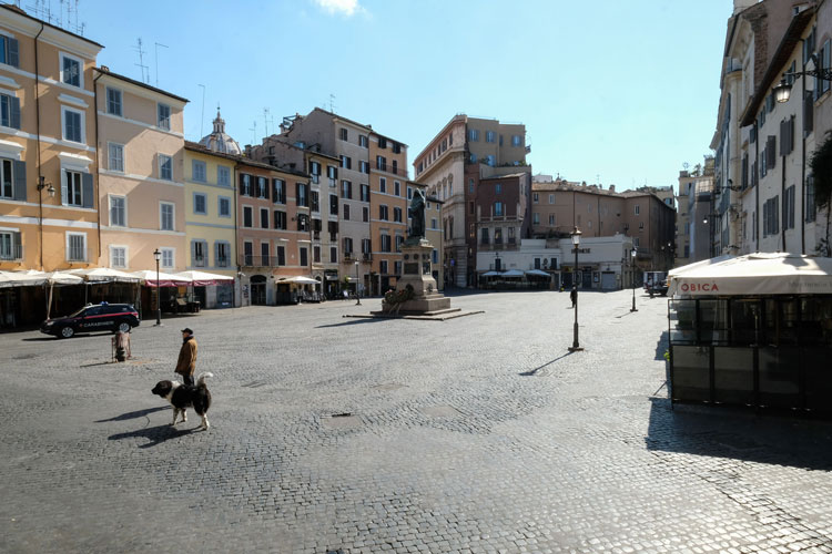 A man walks his dog across a deserted Piazza Campo dei Fiori in central Rome on March 24 during Italy's lockdown aimed at stopping the spread of the coronavirus pandemic.
