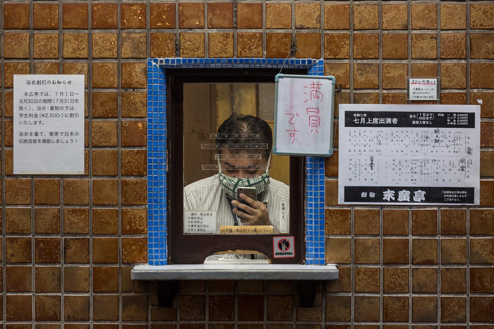 A ticket-clerk checks his phone at Yose theater Shinjuku-Suehirotei on July 10, in Tokyo.
