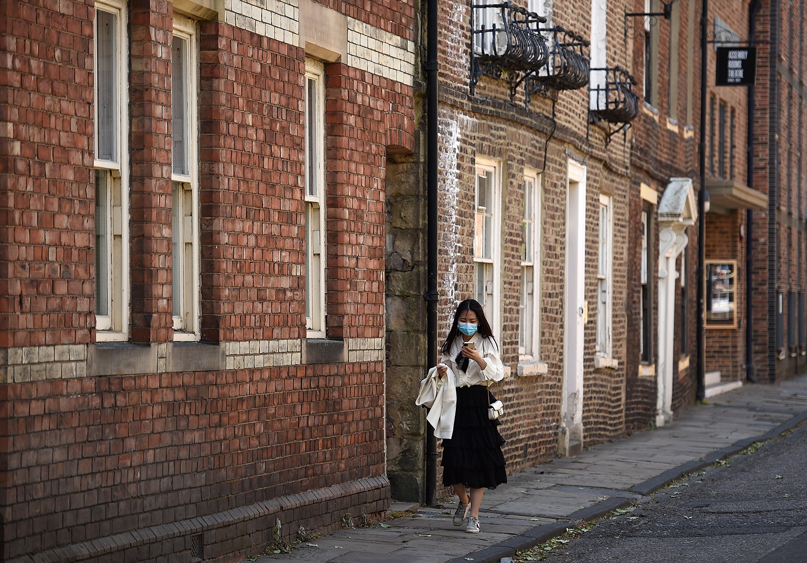 A woman wearing a face mask walks along a street in Durham, north east of England, on May 25.