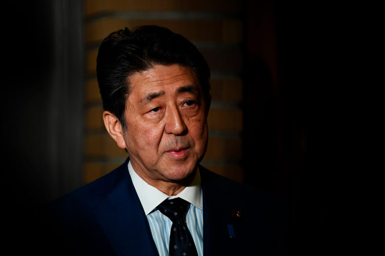Japan's Prime Minister Shinzo Abe talks to journalists in front of the prime minister's residence in Tokyo, Tuesday, March 24, 2020.