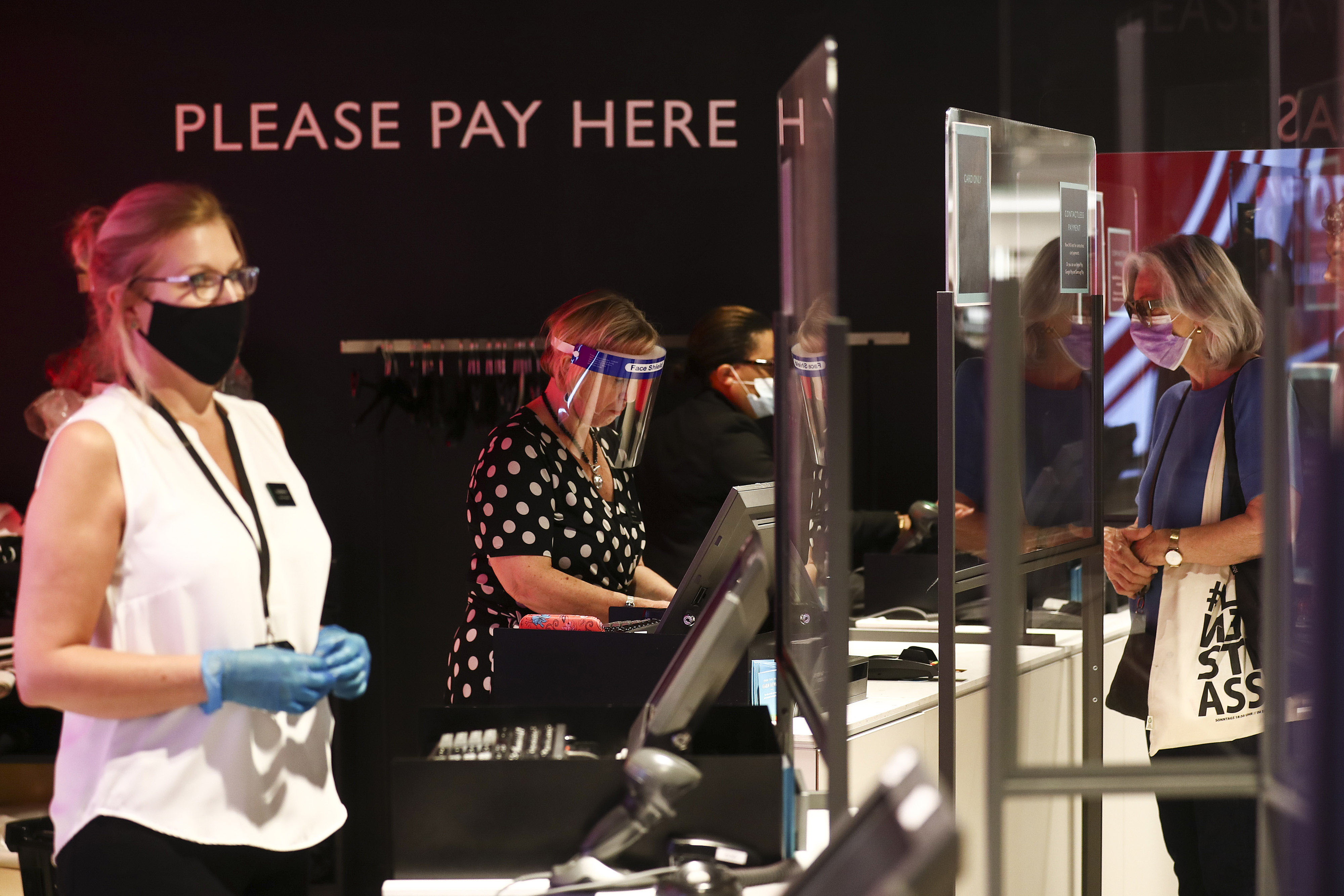 Employees serve customers on July 23 inside a John Lewis Partnership department store in London.