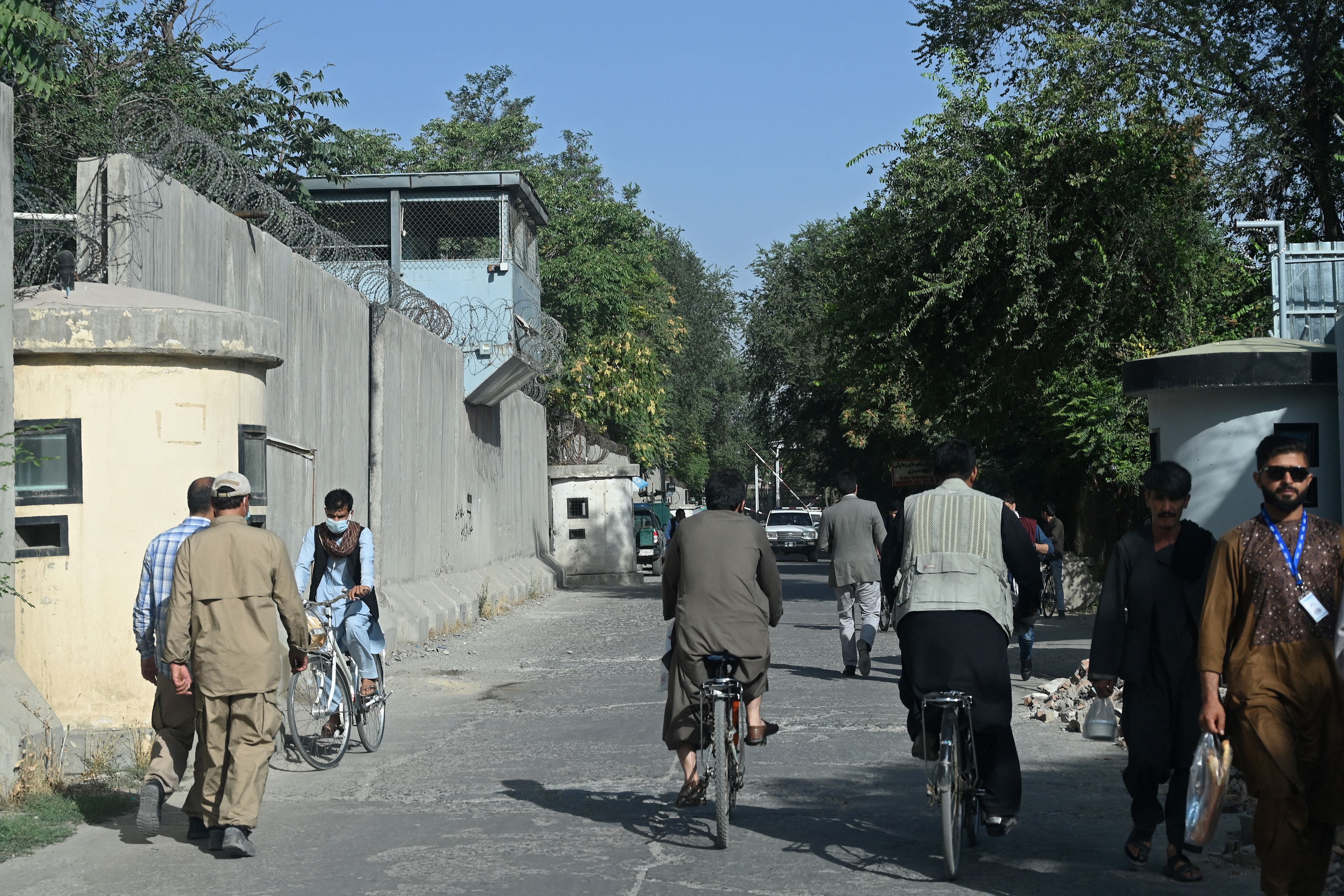 Afghan men walk through a sreet in the Green Zone of Kabul on Sunday.
